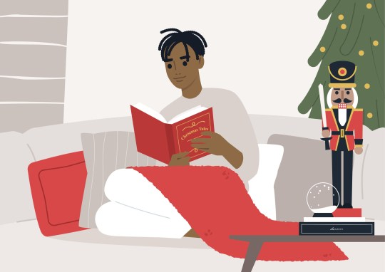 A young male Black character reading a fairy tale Christmas book on a sofa, winter holidays, cozy interior