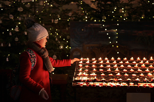 Young girl lighting candle in the church on christmas day