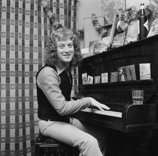 Noddy Holder Of Slade sits at a piano