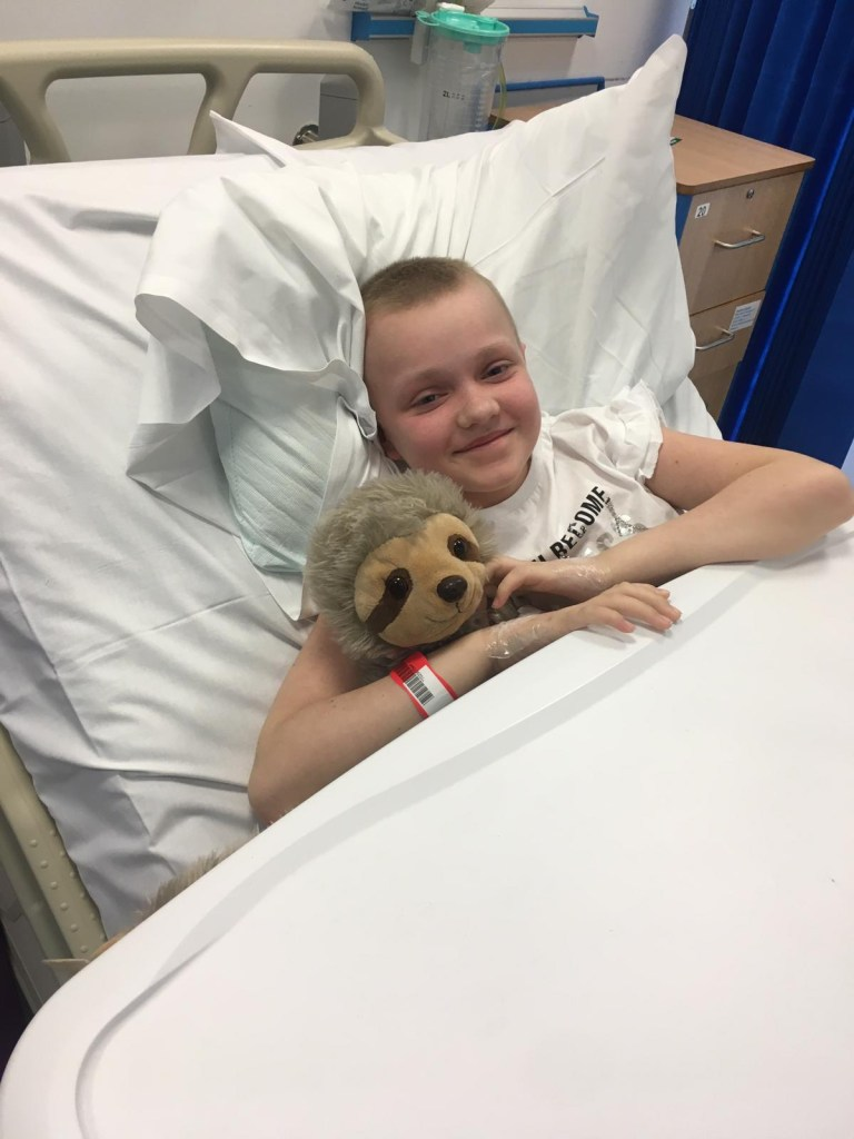 Grace in a hospital bed cuddling Sammy the Sloth