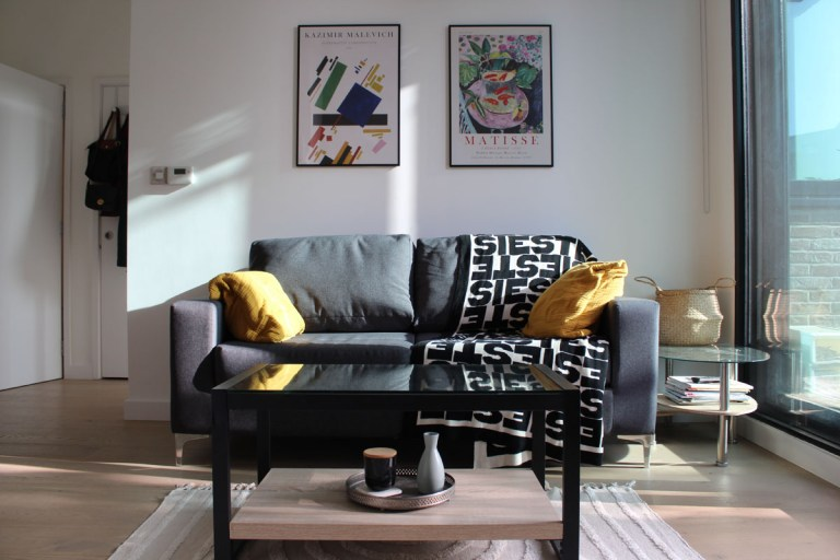 What I Rent: Kelsey, one-bedroom flat in Archway, London - grey sofa with yellow cushions and a black and white throw, plus Matisse prints