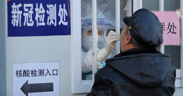 Un échantillon sur écouvillon est prélevé sur un site de test de coronavirus en Chine