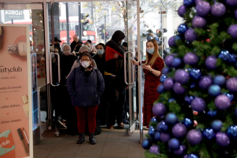 People enter the Debenhams department store, which is expected to close down, after the doors were opened for the day's trading as non-essential shops are allowed to reopen after England's second lockdown ended at midnight, on Oxford Street, in London, Wednesday, Dec. 2, 2020. In another dark day for the British retailing industry, Debenhams said Tuesday it will start liquidating its business after a potential buyer of the company pulled out, a move that looks like it will cost 12,000 workers their jobs. (AP Photo/Matt Dunham)