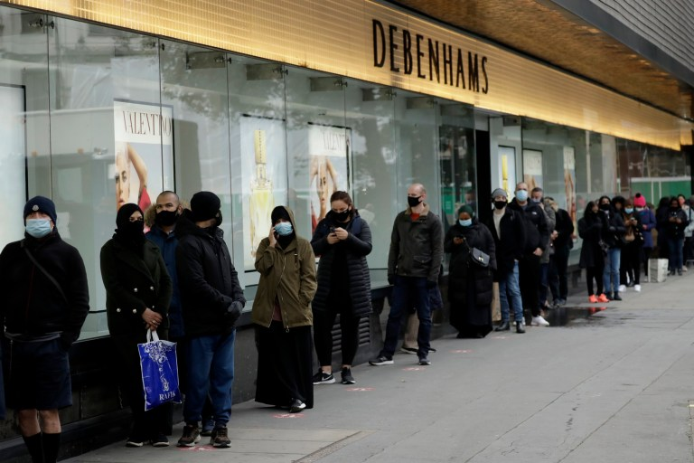 People queue up waiting for the Debenhams department store, which is expected to close down, to open for the day's trading as non-essential shops are allowed to reopen after England's second lockdown ended at midnight, on Oxford Street, in London, Wednesday, Dec. 2, 2020. In another dark day for the British retailing industry, Debenhams said Tuesday it will start liquidating its business after a potential buyer of the company pulled out, a move that looks like it will cost 12,000 workers their jobs. (AP Photo/Matt Dunham)