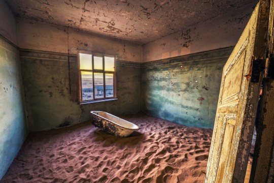 Old bathtub in the ruins of the mining town named Kolmanskop located in the Namib desert near Luderitz in Namibia, Southern Africa