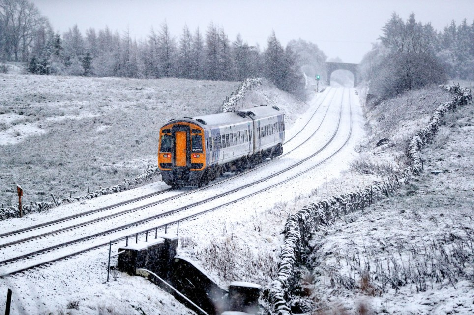 A train runs along the tracks in snowy North Yorkshire