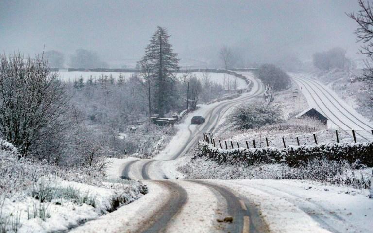 A car is stuck on a snowy road near Garsdale in Cumbria