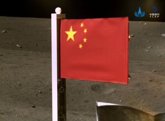 Le drapeau national chinois est vu déployé depuis le vaisseau spatial Chang'e-5 sur la lune, dans cette image fournie par la China National Space Administration (CNSA) le 4 décembre 2020. CNSA / Document via REUTERS ATTENTION EDITEURS - CETTE IMAGE A ÉTÉ FOURNIE PAR UN TIERCE PERSONNE.  PAS DE REVENTE.  PAS D'ARCHIVES.