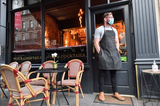 A bartender wearing a face mask stands outside a bar in Cardiff ahead of pubs, bars, restaurants and cafes being forced to stop selling alcohol and shut by 6pm as part of a new round of coronavirus restrictions that come into force in Wales on Friday night. PA Photo. Picture date: Friday December 4, 2020. See PA story HEALTH Coronavirus Wales. Photo credit should read: Ben Birchall/PA Wire