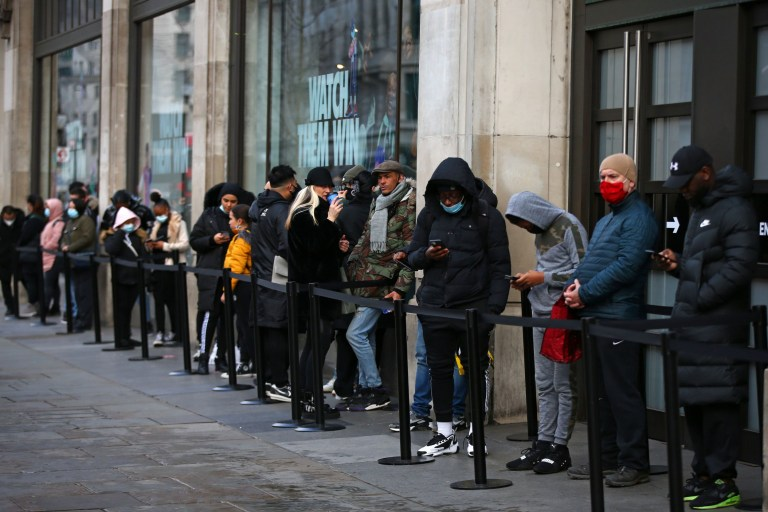 Shoppers queue outside the Nike Town London store on Oxford Street ahead of opening on December 6, 2020.