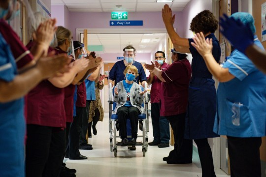 Margaret Keenan, 90, is applauded by staff as she returns to her ward after becoming the first person in the United Kingdom to receive the Pfizer/BioNtech covid-19 vaccine at University Hospital, Coventry, at the start of the largest ever immunisation programme in the UK's history. PA Photo. Picture date: Tuesday December 8, 2020. The UK is the first country in the world to start vaccinating people with the Pfizer/BioNTech jab. See PA story HEALTH Coronavirus. Photo credit should read: Jacob King/PA Wire