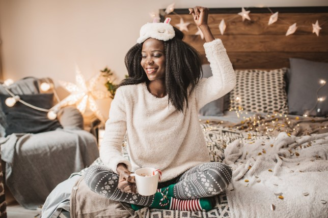 woman on bed happy drinking hot chocolate at christmas