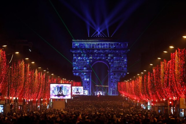 People wait for the new year's eve fireworks at the Arc de Triomphe at Champs Elysees in Paris