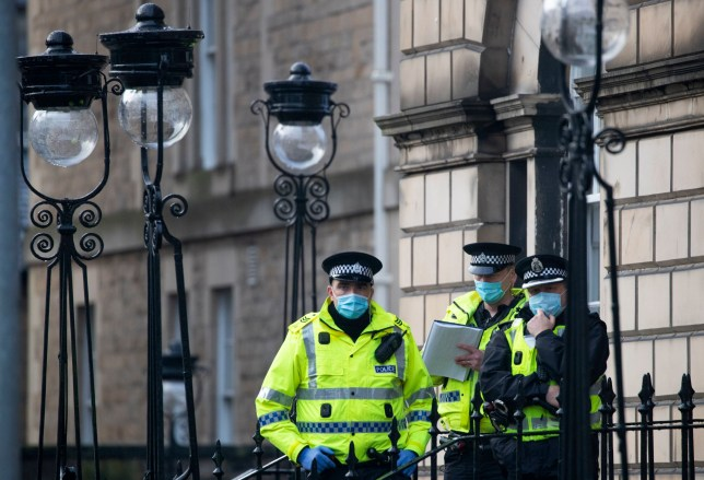 Police outside Bute House in Charlotte Square, Edinburgh watch an anti-lockdown protest. PA Photo. Picture date: Saturday December 12, 2020. The protester was part of the group known as Scotland Against Lockdown who are asking people to listen to real scientific evidence in regard to the health of the general public during the coronavirus pandemic. See PA story SCOTLAND Coronavirus. Photo credit should read: Jane Barlow/PA Wire