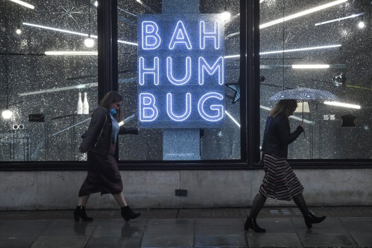 LONDON, ENGLAND - DECEMBER 14: Two women are seen walking past a shop display with a sign reading 'Bah Humbug' on December 14, 2020 in London, England. In 'Tier 3' of England's pandemic-control measures, restaurants and pubs will be limited to takeaway and delivery, although shops are allowed to remain open. (Photo by Peter Summers/Getty Images)