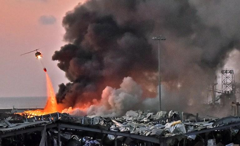 Histoires de 2020: survivre à l'explosion de Beyrouth. Clara. Tom Williams TOPSHOT - Un hélicoptère éteint un incendie sur les lieux d'une explosion dans le port de Beyrouth, la capitale libanaise, le 4 août 2020 (Photo de STR / AFP) (Photo de STR / AFP via Getty Images)