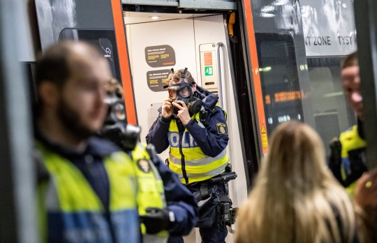 A Swedish police officer adjusts a protective mask at the border control point at Hyllie station, as the Swedish government shut the border after a mutated strain of the coronavirus was discovered in Denmark, in Malmo, Sweden December 22, 2020. TT News Agency/Johan Nilsson via REUTERS ATTENTION EDITORS - THIS IMAGE WAS PROVIDED BY A THIRD PARTY. SWEDEN OUT. NO COMMERCIAL OR EDITORIAL SALES IN SWEDEN.