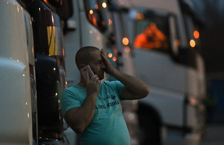 A driver of a freight lorry talk son his phone as he stands outside his cab parked at a truck stop off the M20 leading to Dover, near Folkestone in Kent, south east England on December 22, 2020, after France closed its borders to accompanied freight arriving from the UK due to the rapid spread of a new coronavirus strain.