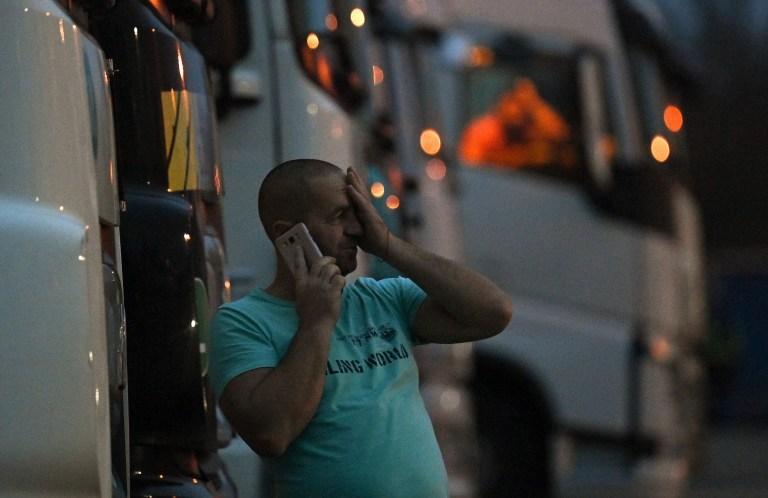 Un chauffeur d'un camion de fret parle à son téléphone alors qu'il se tient à l'extérieur de sa cabine garée à un arrêt de camion sur le M20 menant à Douvres, près de Folkestone dans le Kent, dans le sud-est de l'Angleterre le 22 décembre 2020, après que la France a fermé ses frontières au fret accompagné arrivant du Royaume-Uni en raison de la propagation rapide d'une nouvelle souche de coronavirus.