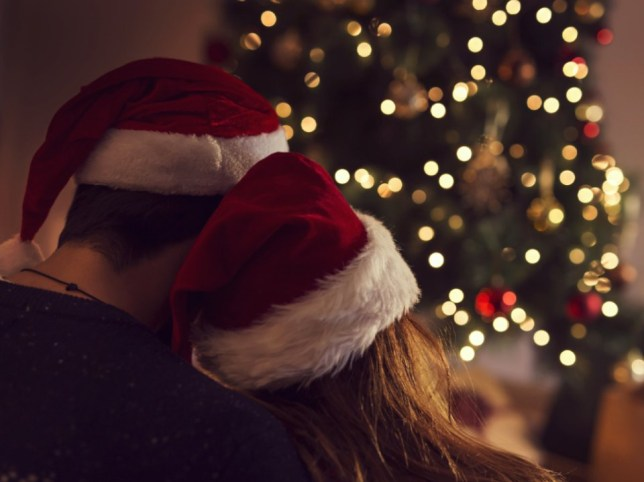 A couple embrace eachother while wearing Santa hats and looking to their Christmas tree.