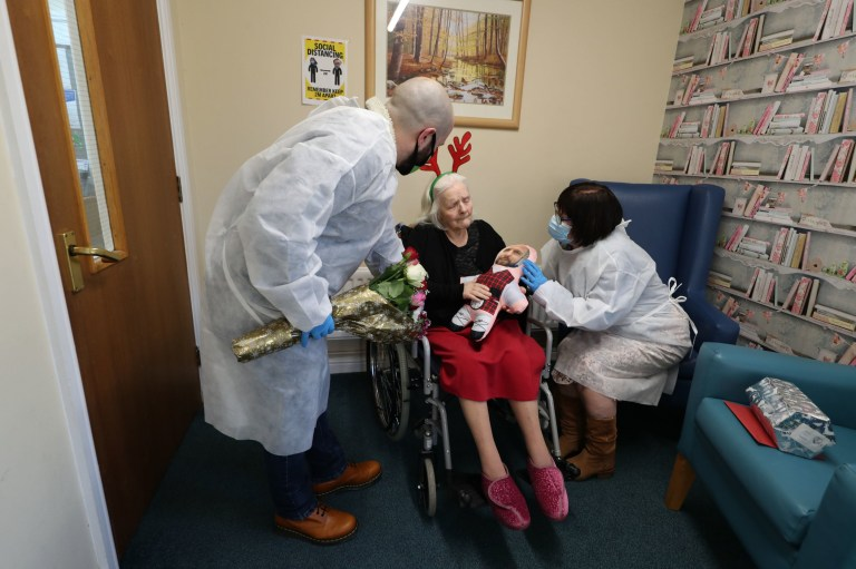 Mary Orme (right) and her son Michael McKimm greet their mother and grandmother, Rose McKimm, during a Christmas Day visit at Aspen Hill Village care home in Hunslet, Leeds. The care home is able to host almost 50 visits for family members this Christmas after running successful trials of lateral flow testing for coronavirus. PA Photo. Picture date: Friday December 25, 2020. See PA story HEALTH Coronavirus. Photo credit should read: Danny Lawson/PA Wire