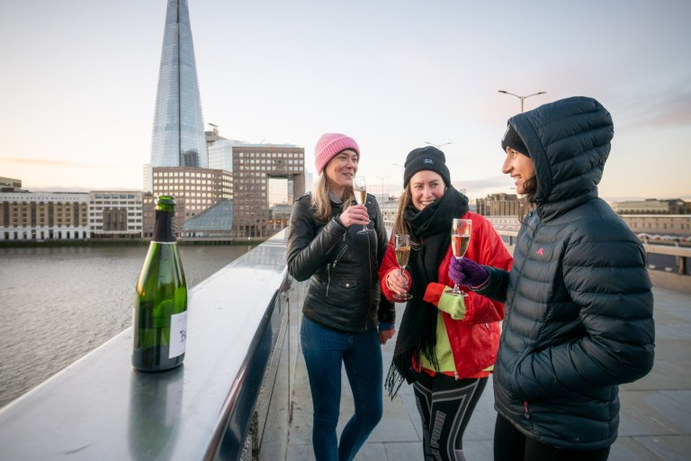 LONDON, ENGLAND - DECEMBER 25: Friends enjoy a glass of Prosecco while watching the sunrise on London Bridge as they welcome in Christmas morning on December 25, 2020 in London, United Kingdom. Last week, the British government scrapped a plan to allow household mixing in England for five days over Christmas. In London and southeast, household mixing was banned, and in other parts of the country indoor meetups were confined to Christmas Day. (Photo by Joseph Okpako/Getty Images)