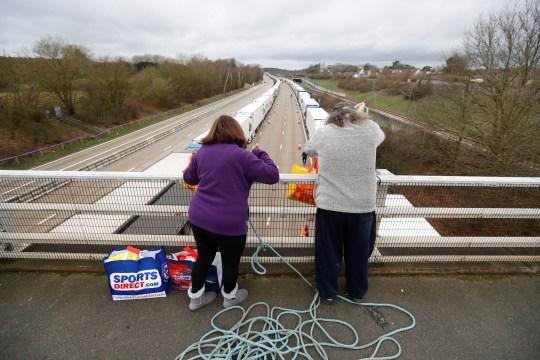 People use a rope to handle supplies to drivers as lorries queue at the M20 motorway near Ashford amid the coronavirus disease (COVID-19) outbreak, Britain, December 26, 2020. REUTERS/Peter Nicholls