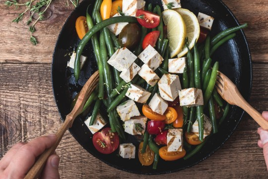 Delicious summer vegan meal, cooking healthy green beans salad with grilled tofu, fresh colorful mix cherry tomatoes, thyme herbs and lemon zest served in rural cast iron skillet, wooden forks, top view