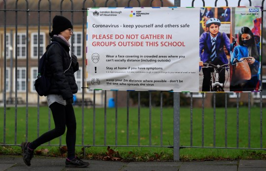 A woman walks past a social distancing health message outside of a secondary school in London, Britain December 29, 2020. REUTERS/Toby Melville