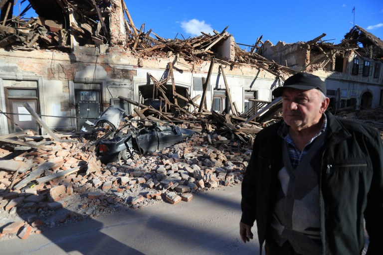 A man stands on a street next to destroyed houses on a street after an earthquake in Petrinja, Croatia December 29, 2020. Slavko Midzor/PIXSELL via REUTERS ATTENTION EDITORS - THIS IMAGE WAS PROVIDED BY A THIRD PARTY. CROATIA OUT. NO RESALES. NO ARCHIVES.