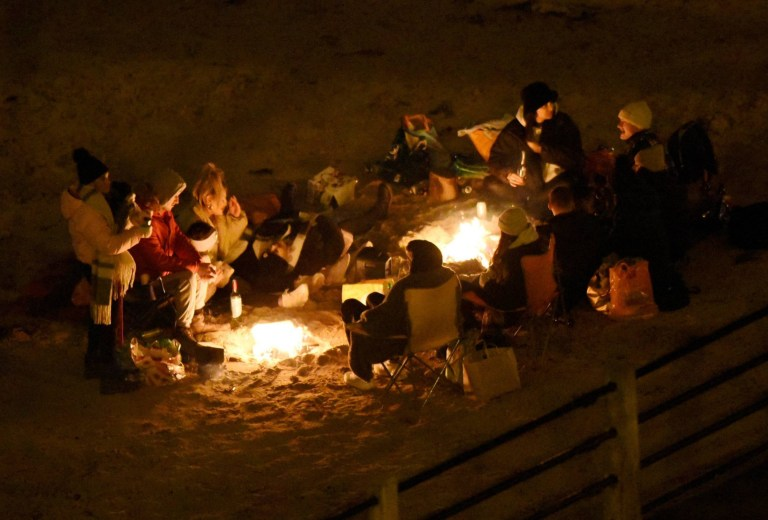 Large groups of people congregate on Tynemouth beach, in North Tyneside