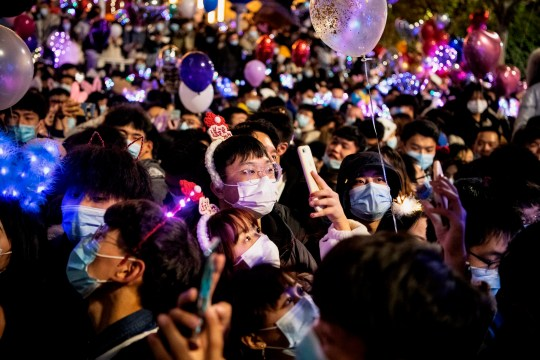 People wearing face masks attend a New Year's countdown in Wuhan in Chinas central Hubei province on December 31, 2020. (Photo by NOEL CELIS / AFP) (Photo by NOEL CELIS/AFP via Getty Images)