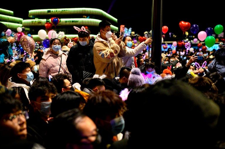 Des personnes portant des masques faciaux assistent au compte à rebours du Nouvel An à Wuhan, dans la province centrale du Hubei en Chine, le 31 décembre 2020 (Photo de NOEL CELIS / AFP) (Photo de NOEL CELIS / AFP via Getty Images)