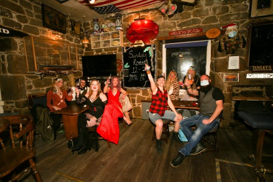 NYE celebrations at the Mermaid pub on St Mary's, Isle Of Scilly. Lucky revellers in Britain???s only Tier 1 area toasted the New Year in pubs ??? but still had to go home before midnight. Scilly Isles locals were the sole Brits able to hit bars for celebrations.