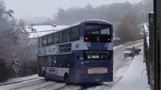 The bus swerves sideways as it slips on a snowy road