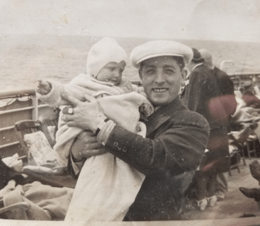 Black and white photo of baby girl being cradled by father on deck of ship