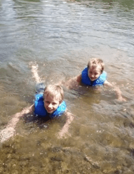 Two young boys bathing in a river