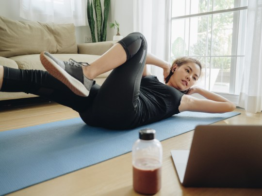 Asian woman working out with laptop at home