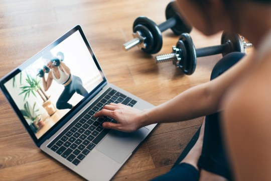 Young Woman Practising Weight Training Workout With A Video Lesson On Laptop.