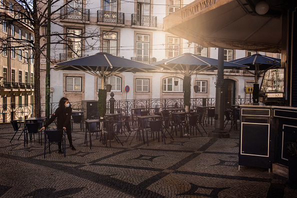 A worker packs away furniture outside a cafe as it closes at Camoes Square in the Chiado district of Lisbon, Portugal