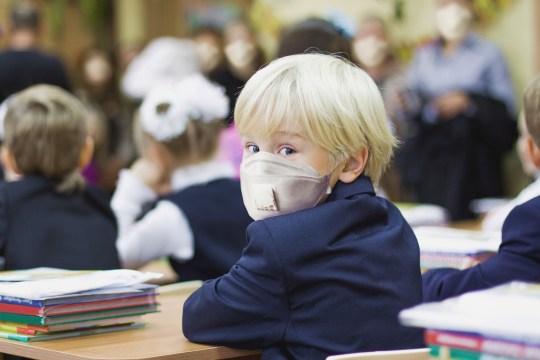 a schoolboy wears a face mask