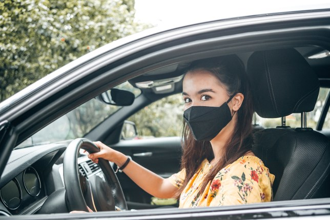 woman wearing a face mask in her car