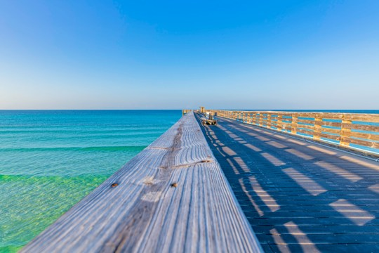 Scenic View Of Wooden Pier Against Clear Blue Sky And The Gulf Of Mexico