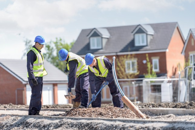 Three builders working in front of a house