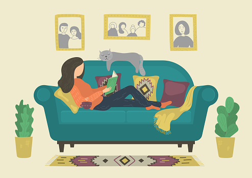 Woman reading book on sofa