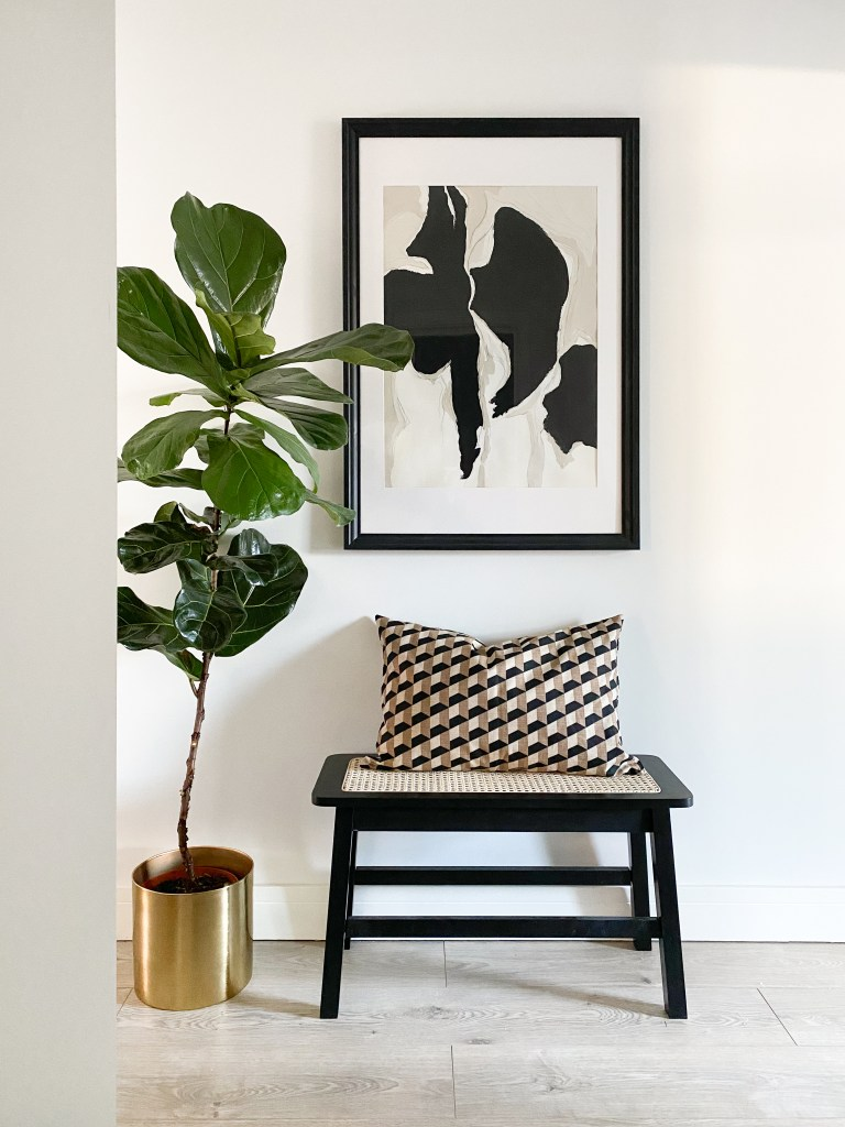 What I Rent: Annabel, two-bedroom flat in Angel, Islington - hallway in home, with stool, large plant, and print hanging on wall
