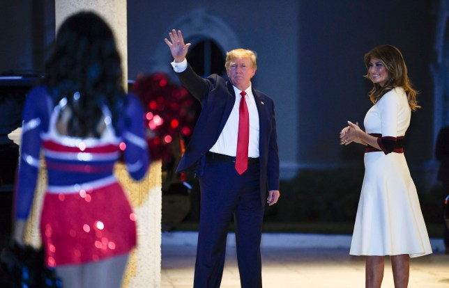Donald Trump watches a cheerleader perform while Melania smiles