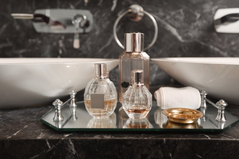 perfume bottles on tray by sinks