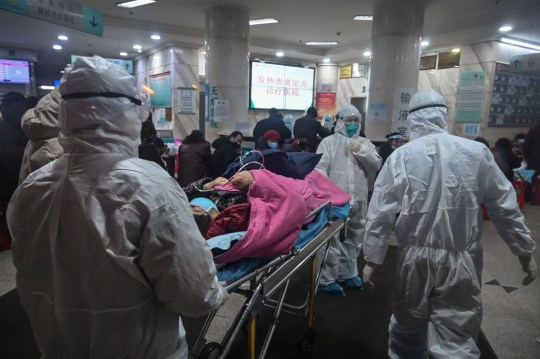 Tom Williams TOPSHOT - In this photo taken on January 25, 2020, medical staff wearing protective clothing to protect against a previously unknown coronavirus arrive with a patient at the Wuhan Red Cross Hospital in Wuhan. - The number of confirmed deaths from a viral outbreak in China has risen to 54, with authorities in hard-hit Hubei province on January 26 reporting 13 more fatalities and 323 new cases. (Photo by Hector RETAMAL / AFP) (Photo by HECTOR RETAMAL/AFP via Getty Images)