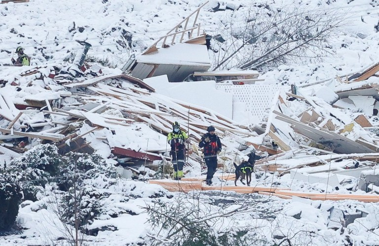 Flattened homes lie covered in snow as rescue crews work with a dog in the landslide area at Ask, Gjerdrum, Norway January 2, 2021. NTB/Erik Schroeder via REUTERS ATTENTION EDITORS - THIS IMAGE WAS PROVIDED BY A THIRD PARTY. NORWAY OUT. NO COMMERCIAL OR EDITORIAL SALES IN NORWAY.